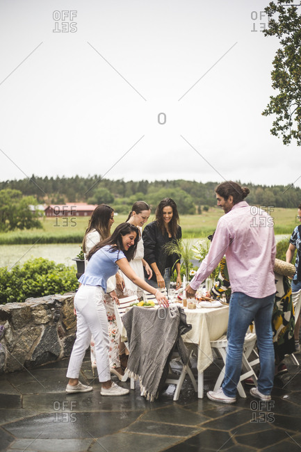 Multi-ethnic friends smiling while standing around dining table in backyard during dinner party