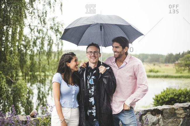 Happy friends standing below umbrella during weekend getaway