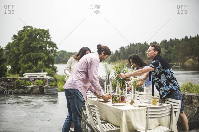 Multi-ethnic friends setting table for dinner party in backyard against clear sky