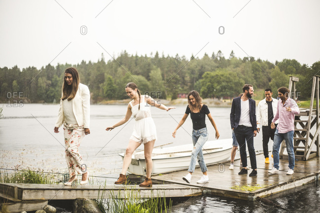 Multi-ethnic friends on jetty over lake during weekend getaway
