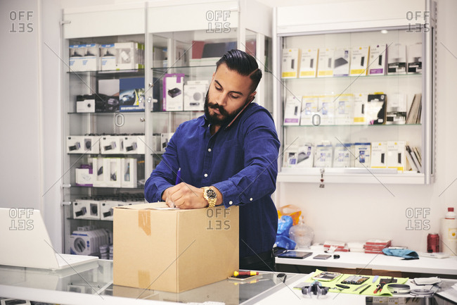Male owner talking on mobile phone while packing box at counter in electronics store