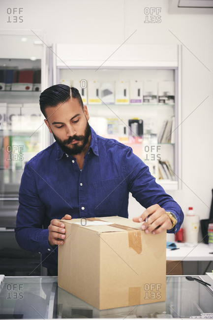 Male owner packing box at counter in electronics store