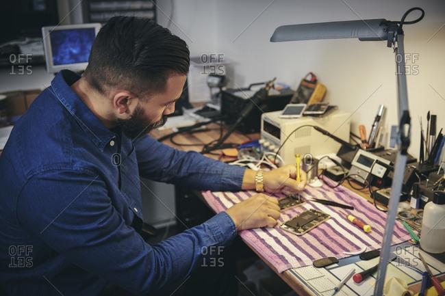 Male engineer repairing mobile phone at table in workshop