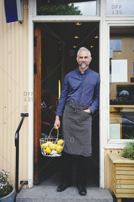 Portrait of confident salesman holding fruit basket while standing at store entrance