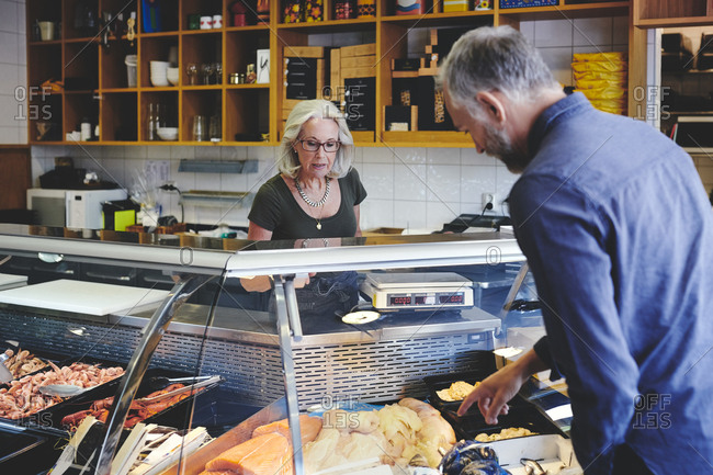 Customer showing seafood at retail display to saleswoman in deli