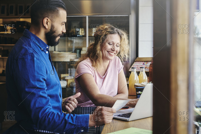Colleagues smiling with discussing over laptop at table in deli