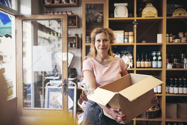 Portrait of confident saleswoman carrying cardboard box against rack in deli