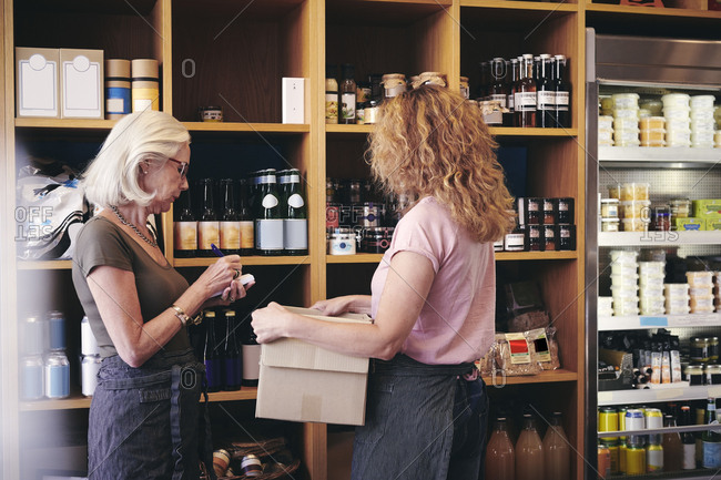 Female colleagues working by rack in deli