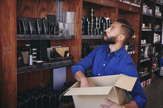 Salesman looking up while unpacking cardboard box in deli