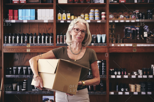 Portrait of senior saleswoman carrying box while standing against rack in deli
