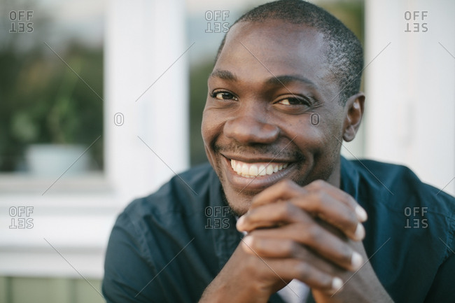 Portrait of smiling mid adult man with hands clasped