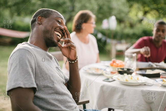 Mid adult man smiling while sitting by table during garden party