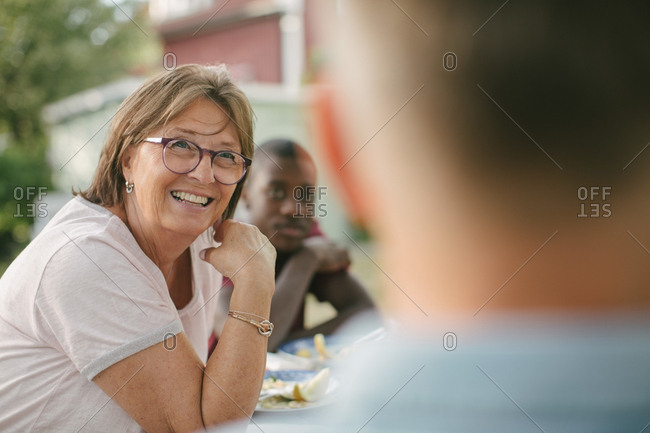 Smiling senior woman looking away while sitting at table during garden party