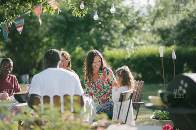 Happy multi-generation family having lunch together at patio during garden party