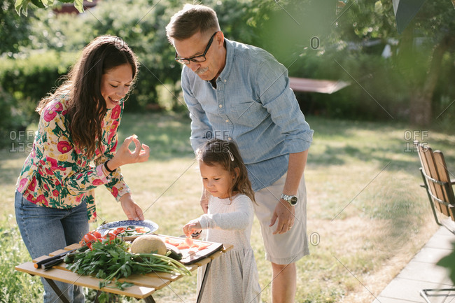 Girl cutting food while standing by mother and grandfather at table in backyard