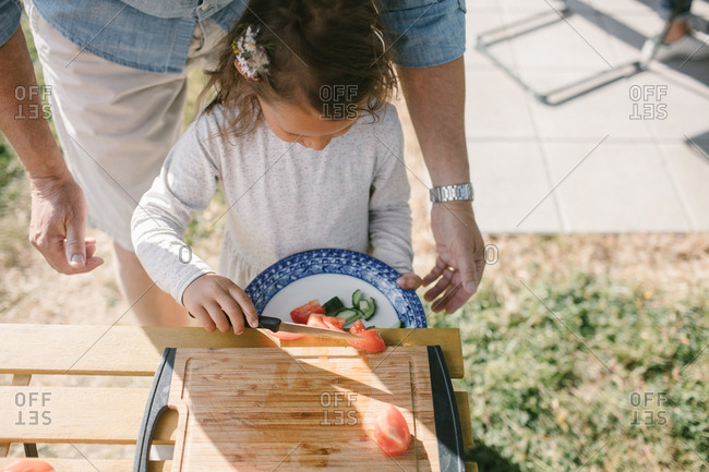 Girl putting tomato slices on a plate with a knife while standing by grandfather at table