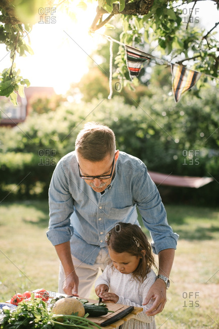 Grandfather assisting granddaughter in cutting vegetable at table in backyard