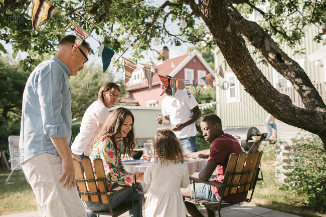 Family looking at girl standing at table in backyard during garden party