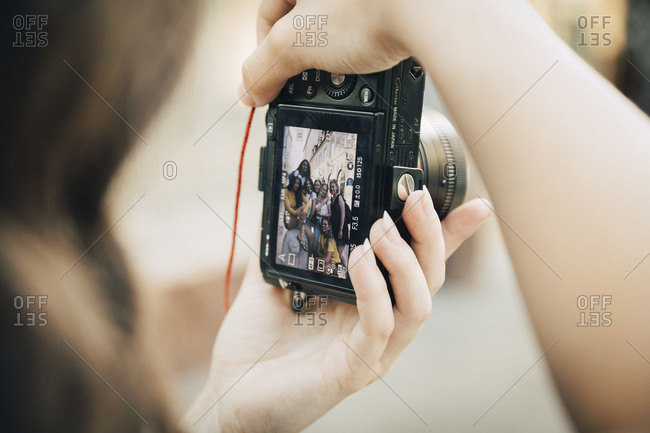 Happy friends posing in city seen on SLR camera screen