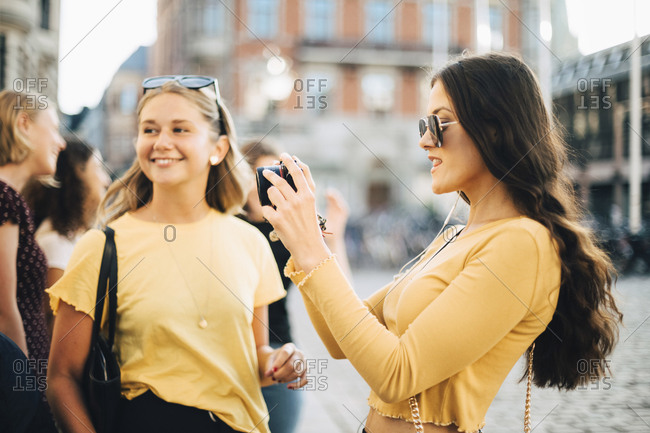 Woman photographing through SLR camera while standing with friends in city