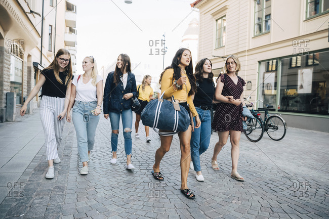 Full length of female friends talking while walking on city street