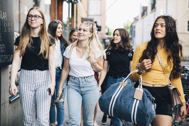 Friends doing window shopping while walking on sidewalk in city