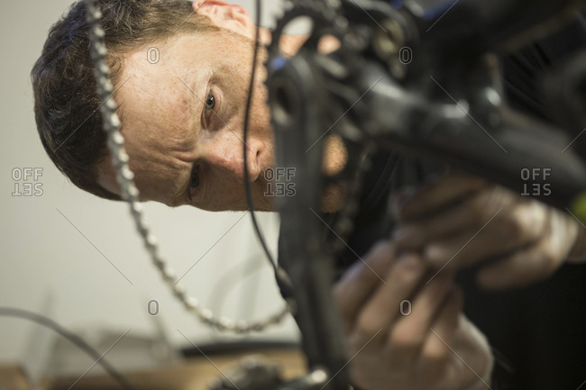 Close-up of serious mechanic wearing gloves while repairing bicycle