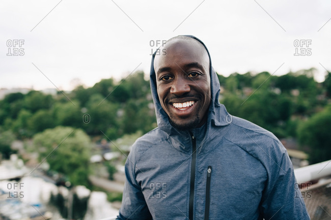 Portrait of confident male athlete standing on footbridge