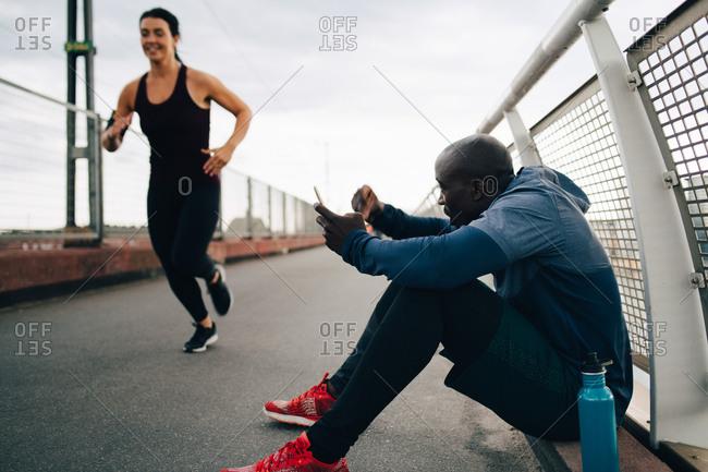 Sportsman holding mobile phone while cheering female athlete running on footbridge