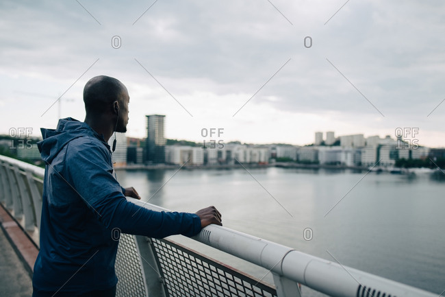 Side view of sportsman looking at city while standing on footbridge over sea against sky