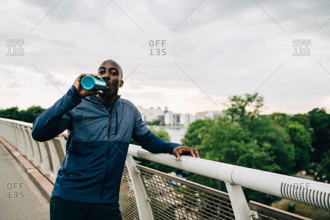 Portrait of thirsty sportsman drinking from bottle while standing on footbridge against sky
