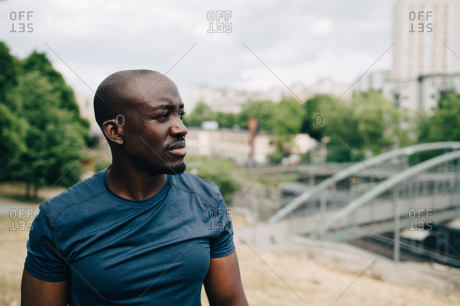 Mid adult sportsman looking away while standing outdoors in city