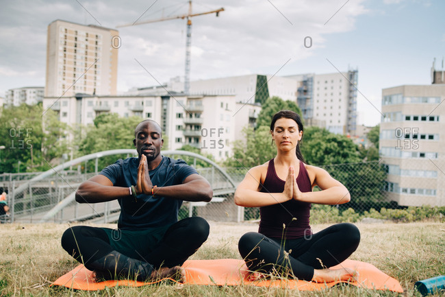 Multi-ethnic friends practicing yoga on field against buildings in city