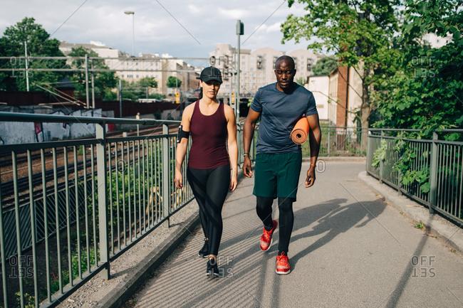 Multi-ethnic male and female athletes talking while walking on footbridge in city