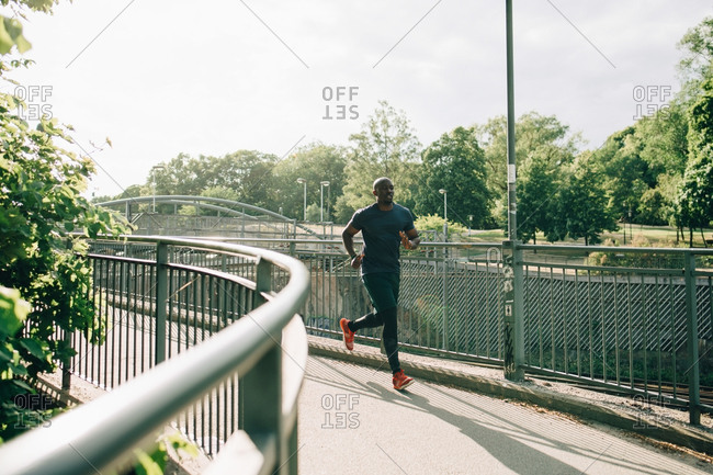 Full length of mid adult sportsman jogging on footbridge in city during sunny day