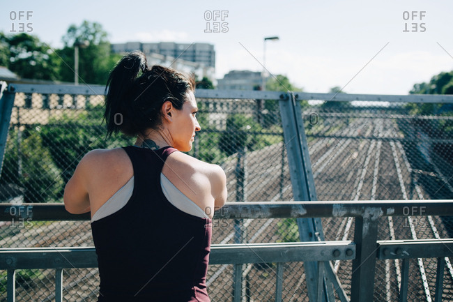 Rear view of exhausted sportswoman leaning on railing at bridge