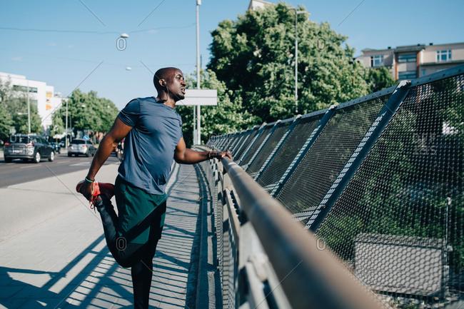 Mid adult sportsman stretching leg by railing on bridge in city