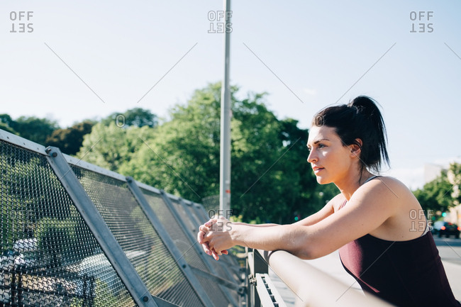 Side view of exhausted sportswoman leaning on railing at bridge