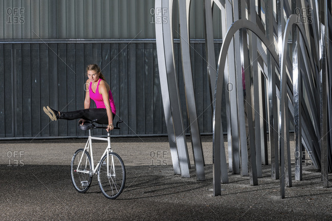 Woman, 19 years old, cycling with artificial wheel, outdoors