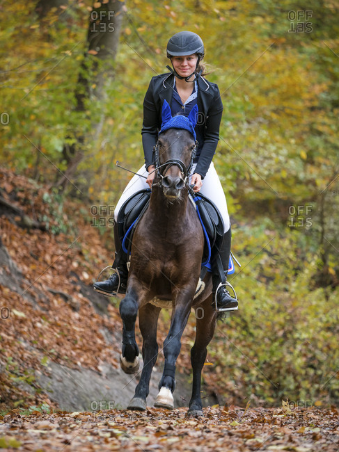 Young woman rides on a forest way in autumn