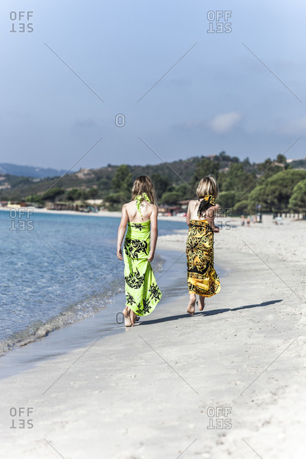 Two girls in beach dresses walking on the sandy, lonely beach of Palombaggia, Corsica