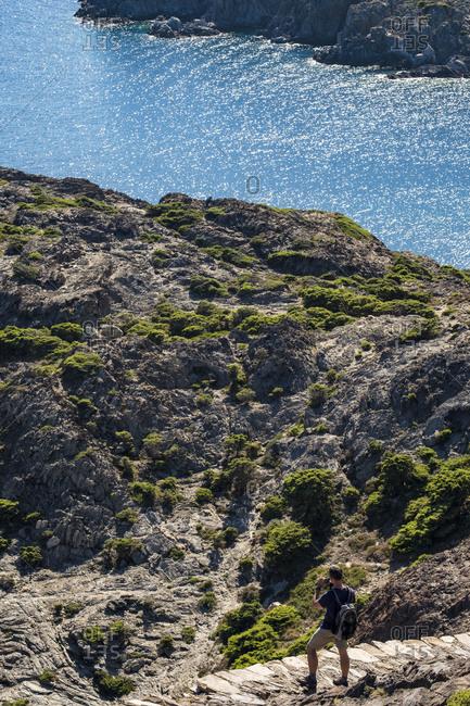 Tourist touring the coastline of the Cap de Creus natural reserve through the Caminos de Ronda north of the Costa Brava in the province of Gerona in Catalonia Spain