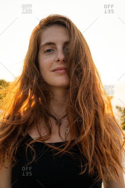 Attractive young female smiling and looking at camera while standing on blurred background of amazing nature on sunny day in Bulgaria, Balkans