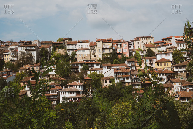 Beautiful houses and trees located on slope of hill on wonderful cloudy day in Bulgaria, Balkans