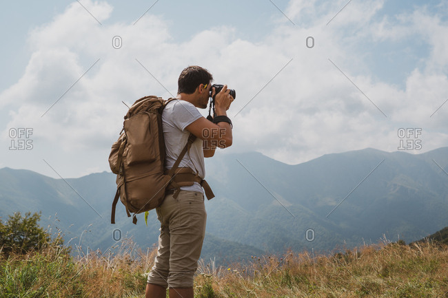 Back view of man with backpack using professional camera to make photos of picturesque countryside in Bulgaria, Balkans