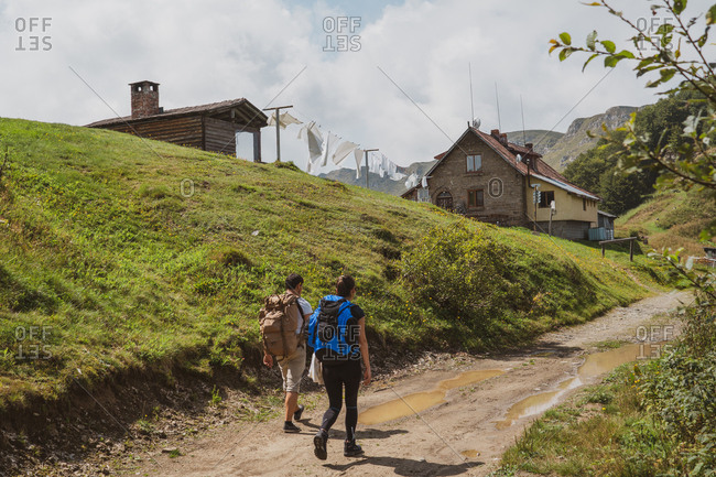 Back view of two people with backpacks walking along countryside path towards lovely houses in majestic countryside on cloudy day in Bulgaria, Balkans