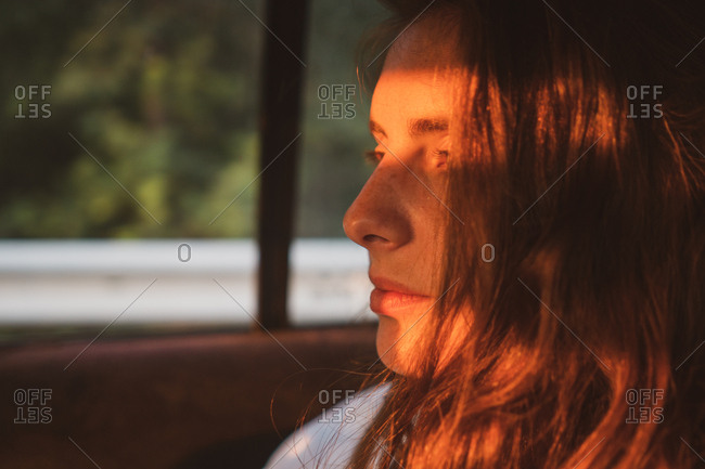 Side view of pretty young female keeping eyes closed while sitting inside modern vehicle during trip through Bulgaria, Balkans
