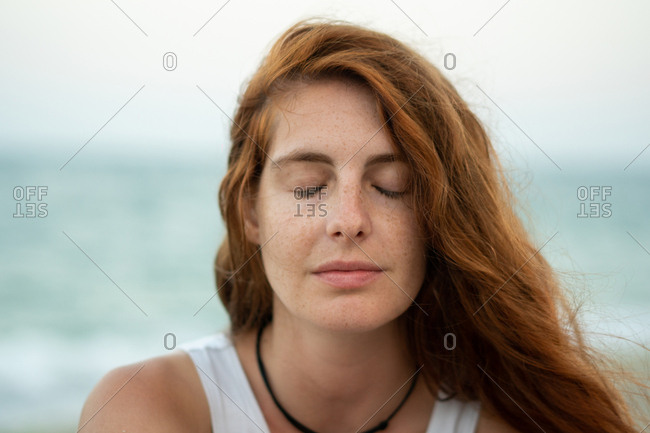 Beautiful young woman with ginger hair looking away while standing on blurred background of beach and sea in Tyulenovo, Bulgaria