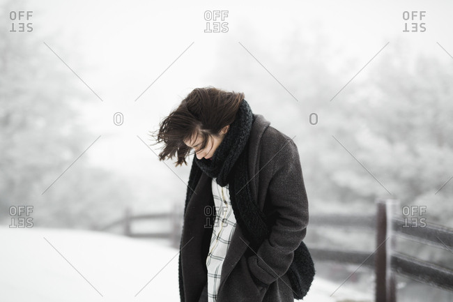 Side view of young female in warm clothes walking near fence on windy winter day in magnificent countryside