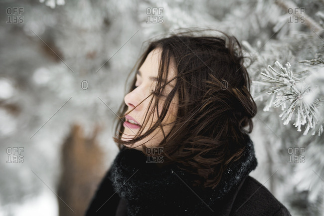 Young female in warm clothes walking on windy winter day in magnificent countryside